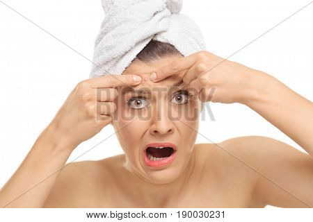 Shocked young woman squeezing a pimple on her forehead isolated on white background