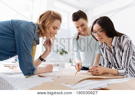 Effective cooperation. Three pretty women standing around the table and considering the placement of patterns while one of them pointing at them with a pencil