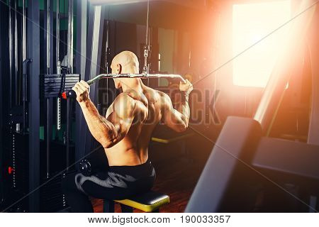 very power athletic guy bodybuilder, execute exercise with gym apparatus, on broadest muscle of back poster