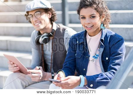 Happy together. Portrait of cheerful teenage girl is sitting on steps with her boyfriend. They are holding gadgets and looking at camera with joy. Focus on young lady