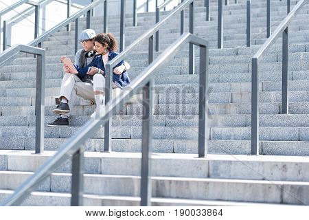 Tender embrace. Low angle of positive romantic lovers are sitting on steps with gadget and smiling. Stylish guy is hugging charming girl. Copy space in the right side