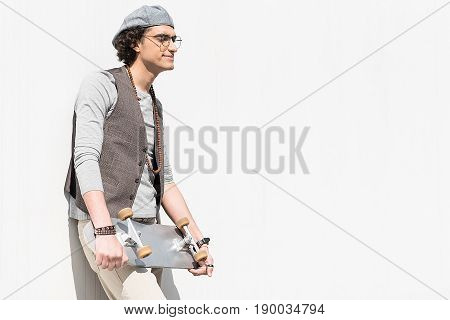 Daydreaming. Positive young guy is leaning on white wall while holding skateboard with smile. He is standing with closed eyes. Copy space in the right side