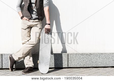 Active rest. Young man is leaning on white wall and holding skateboard. His hand is on pocket and his legs are crossed. Copy space in the right side