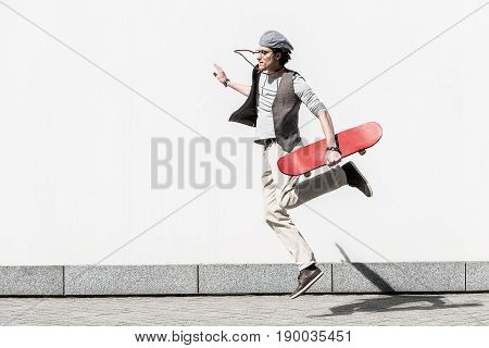 In midair. Young energetic guy is doing trick against white wall. He is jumping while holding red skateboard. Copy space in the left side
