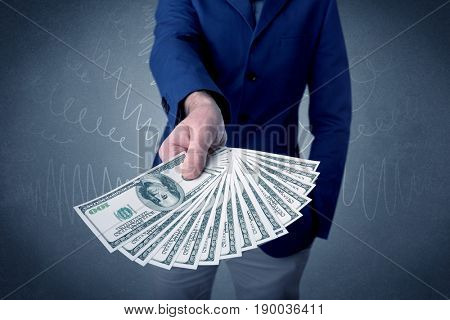 Young businessman holding large amount of bills with grungy background