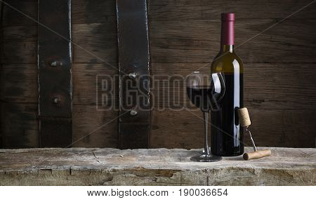 red wine bottle and wine glass on wodden barrel.