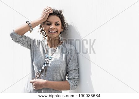 Bright smile. Waist up portrait of cheerful curly girl is leaning on white wall. She is posing with smile while holding hand on her head. Copy space in the right side