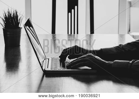 Laptop over a wooden desk. Man typing on the keyboard.