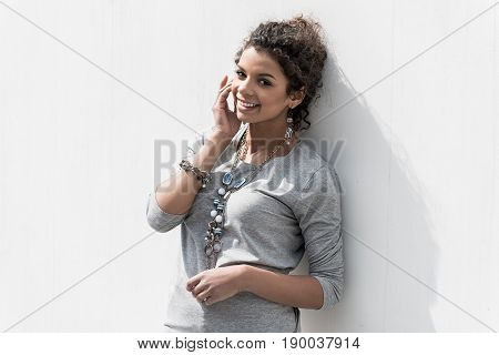 Involved in jubilation. Portrait of cheerful positive girl is smiling and holding her hand near face while expressing gladness. She is looking at camera with joy