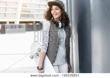 Revel in skating. Cheerful young hipster girl is holding skateboard and expressing positivity while standing outdoors and looking aside joyfully