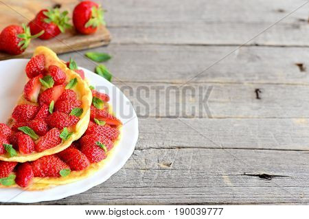 Sweet strawberry omelette. Colorful omelette stuffed with fresh strawberries and garnished with mint on a plate and wooden background with empty place for text. Summer breakfast or lunch idea