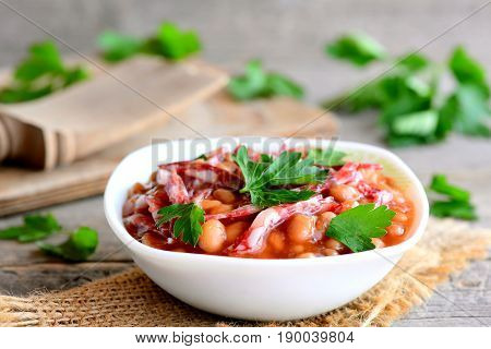 Sausage and bean stew. Easy white bean stewed with smoked sausage, tomato sauce and parsley leaves in a bowl and on a wooden table. Home nutritious stew. Rustic style