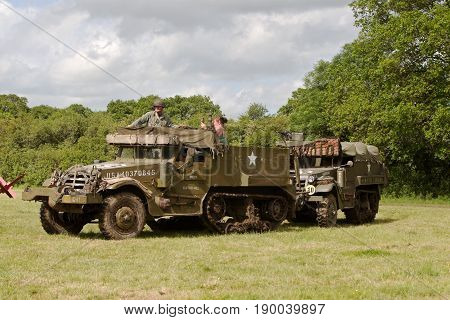 DENMEAD, UK - MAY 25: A pair of WW2 ex USA halftracks make their way around the arena having just completed their part in the Overlord shows grand finale battle re-enactment on May 25, 2014 in Demead