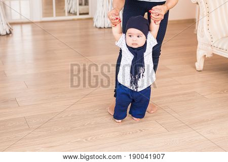 baby taking first steps with mother help,
