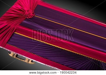 closed red and purple coffin covered with elegant cloth isolated on gray background. coffin close-up on royal background. Ritual objects for burial. Surrender body dust of the earth. Christian funeral ritual