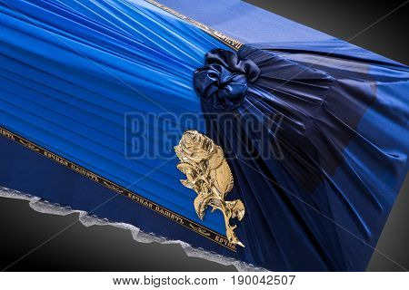 closed blue coffin covered with cloth isolated on gray background. coffin close-up on royal background. Ritual objects for burial. Surrender body dust of the earth. Christian funeral ritual