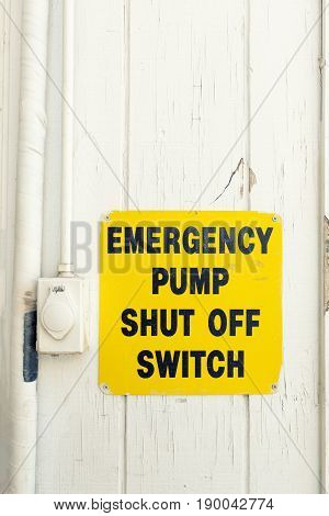 Emergency pump shut off or stop push button switch sign on wood board with filter effect