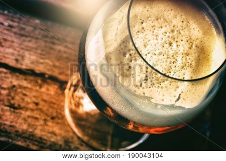 Glass of fresh beer in rustic pub top view. Food and drink background
