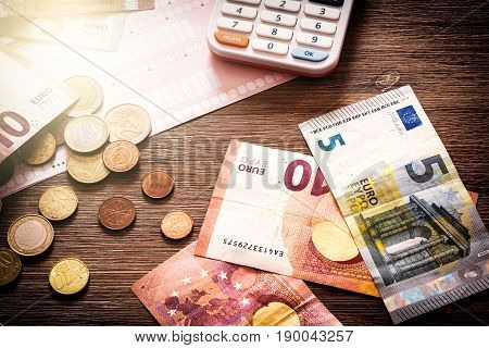 Euro banknotes and coins with bills to pay. Finances and budget concept