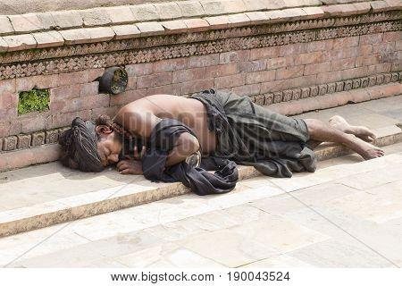 KATHMANDU NEPAL - SEPTEMBER 29 2016 : Beggar Sadhu holy man asleep on the sidewalk on a street near Pashupatinath Temple in Kathmandu Nepal
