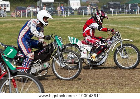 PUTTENHAM, UK - JULY 14: Riders competing in the Puttenham grasstrack event leave the start line at speed in one of the solo rider heats on July 14, 2013 in Puttenham.