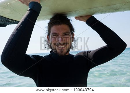 Portrait of smiling surfer in wetsuit carrying surfboard over head at beach coast