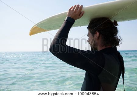 Surfer in wetsuit carrying surfboard over head at beach coast on a sunny day