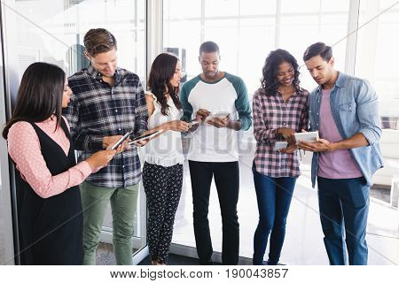 Business people using tablet pcs while standing by window in office