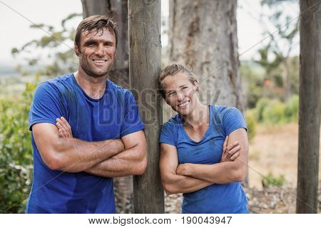 Smiling man and woman standing with arms crossed during obstacle course in boot camp
