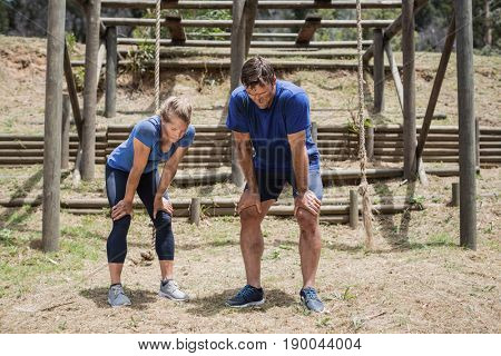Tired man and woman bend down with hands on knees during obstacle course in boot camp