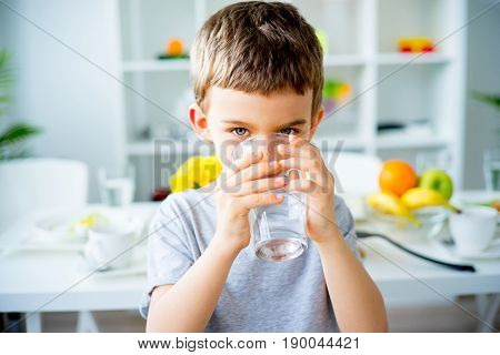 The child drinks clean water at home