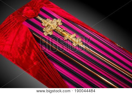 closed pink coffin covered with cloth isolated on gray background. coffin close-up with gold Church cross on royal background. Ritual objects for burial. Surrender body dust of the earth. Christian funeral ritual