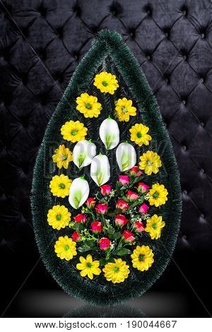Luxury Funeral wreath with colorful flowers isolated on royal dark background. Ritual object for funeral
