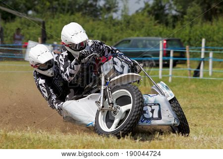 PUTTENHAM, UK - JULY 14: An unnamed sidecar team speed around the top corner of the circuit in first place during the Puttenham grasstrack meeting on July 14, 2013 in Puttenham.