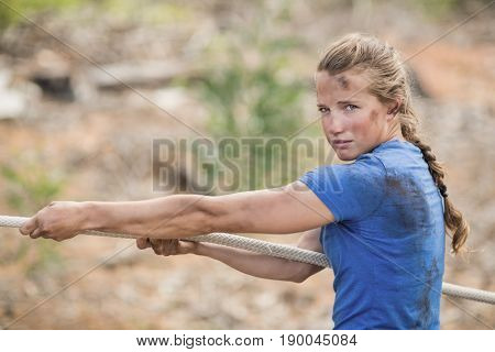 Woman playing tug of war during obstacle course in boot camp