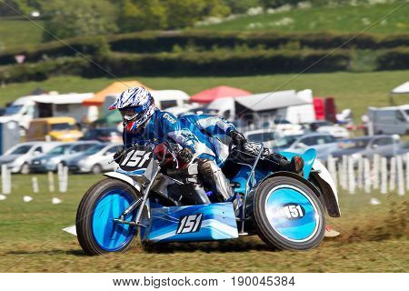 ALVELEY,UK - MAY 7: A sidecar team competing in the Bewdley MCC spring grasstrack meeting accelerate out of the slight uphill corner at speed on May 7, 2017 in Alveley