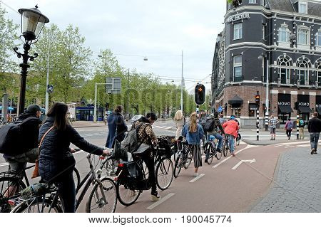 AMSTERDAM NETHERLANDS - MAY 15 2017: Queue of cyclists in front of a special traffic light on the bike path