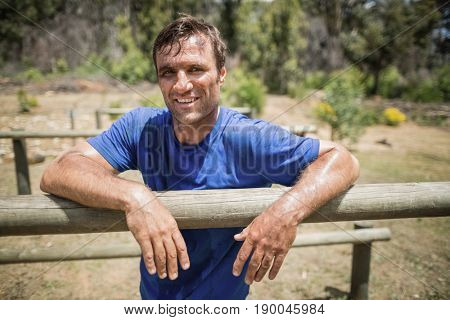 Smiling man leaning on a hurdle during obstacle course in boot camp