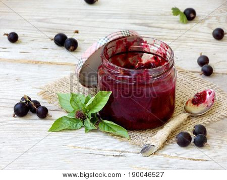 One Jar Of Jam From The Black Currant On A Wooden Background. Berries Frayed With Sugar