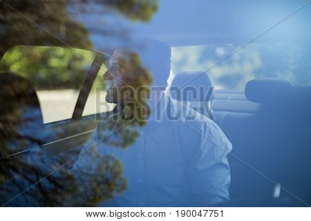 Man sitting on back seat seen through car windshield