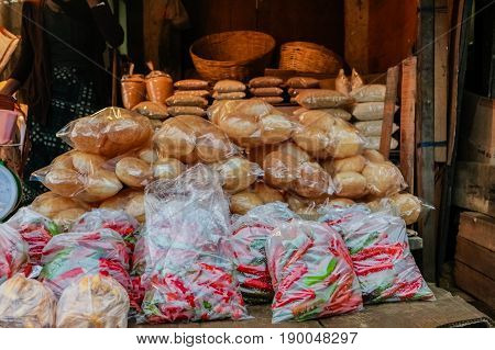 Packed red hot chili peppers and rolls on shelf in a local Bhutanese marketplace