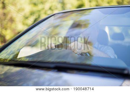 Man driving car seen through windshield