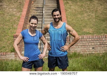 Portrait of fit man and woman standing with hands on hip against staircase in boot camp