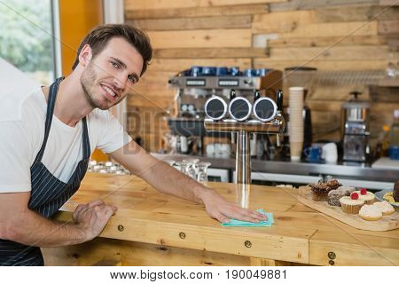 Portrait of waiter cleaning counter worktop in café