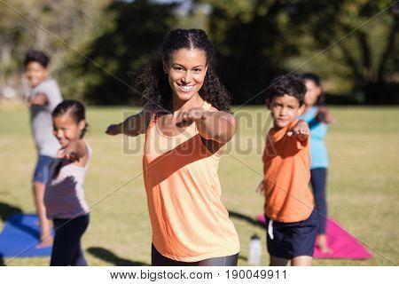 Portait of happy female trainer teaching Virabhadrasana II pose