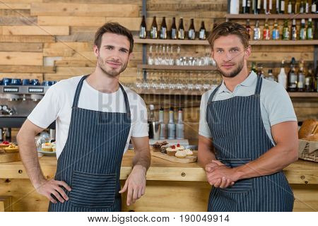 Portrait of smiling waiters standing at counter in café