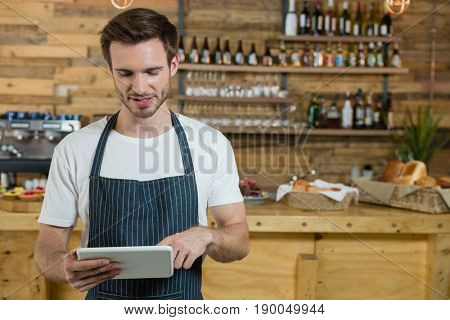Waiter using digital tablet at counter in café
