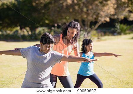 Young female trainer examining children praciticing Virabhadrasana II pose on mat
