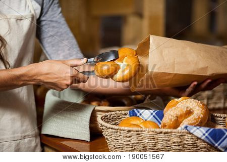 Mid-section of staff packing bread in paper bag at bakery shop