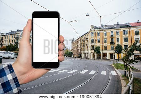 Man's hand with a phone on a background of city streets in Europe.  White screen, you can insert your own image or text here.